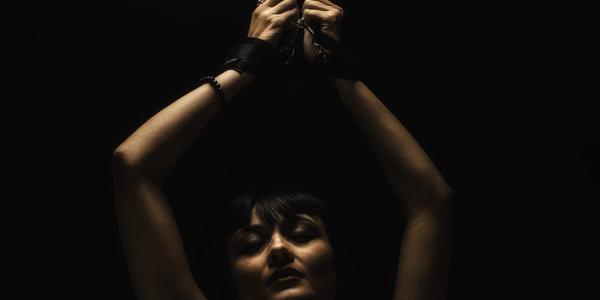 手を縛られて拘束される女性
